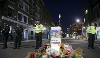 Police officers on duty stand next to floral tributes on Southwark Street in London, Sunday, June 4, 2017, near the scene of Saturday's attack. A series of attacks described as terrorism killed several people and injured dozens on Saturday. (Yui Mok/PA via AP)