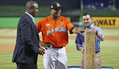 Miami Marlins president of baseball operations Michael Hill, left, and Marlins president David Samson, right, present pitcher Edinson Volquez with the previous game's pitching rubber in honor of Volquez' no-hitter in that game, during a presentation before the start of a baseball game against the Arizona Diamondbacks, Sunday, June 4, 2017, in Miami. (AP Photo/Wilfredo Lee)