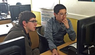 ADVANCE FOR WEEKEND EDITIONS, JUNE 3-4 - In this May 2017 photo, University of Puget Sound sophomore Jake Redman, left, assists Lincoln High School student Antony Vo at Lincoln High School in Tacoma, Wash. Redman is part of Beta Coders, a group from the University of Puget Sound that tutors Lincoln students. (Brooke Thames/The News Tribune via AP)