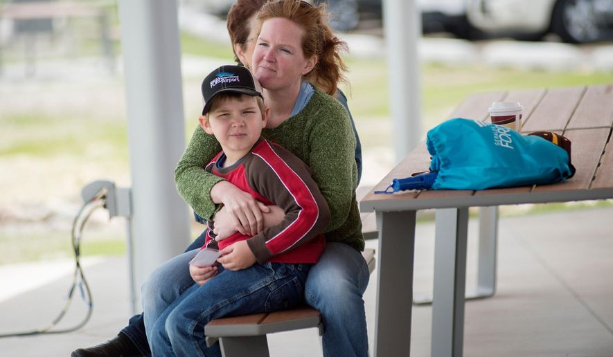 In this Wednesday, May 31, 2017 photo, Jennifer Zirkle holds her son, James Rykse, at the Gerald R. Ford International Airport Viewing Area ribbon cutting at the airport in Grand Rapids, Mich. The ribbon cutting celebrated the new pavilion, picnic tables and bathroom facilities.(Neil Blake /The Grand Rapids Press via AP)