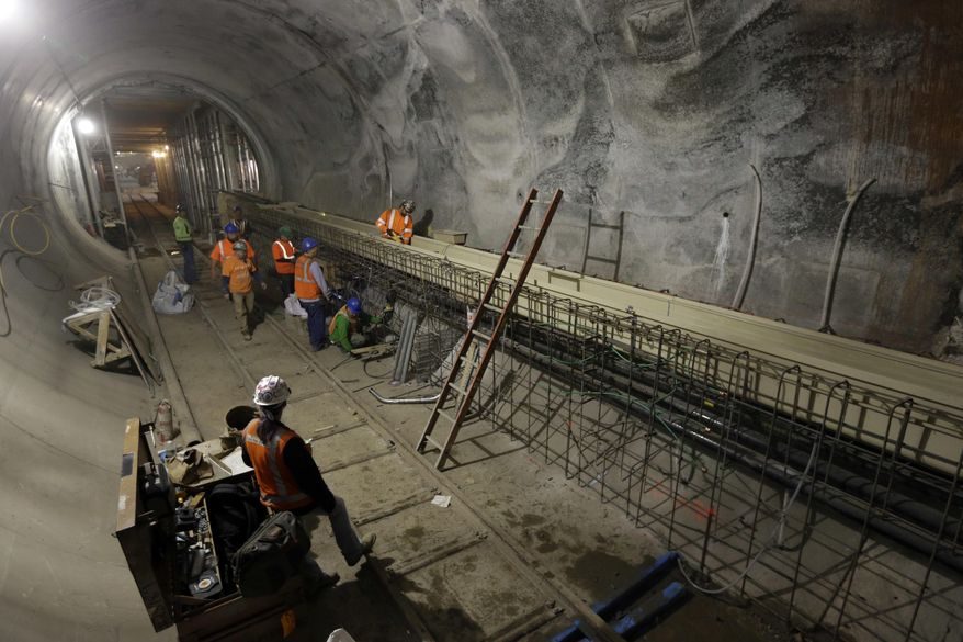 FILE - In this Nov. 4, 2015, file photo, contractors work on the East Side Access project beneath midtown Manhattan, in New York. The agency that runs the Long Island Rail Road, the busiest commuter railroad in the U.S., has spent more than a decade carving out tunnels and a massive subterranean cavern that will bring suburban trains beneath the East River to Grand Central in Manhattan. (AP Photo/Mary Altaffer, File)