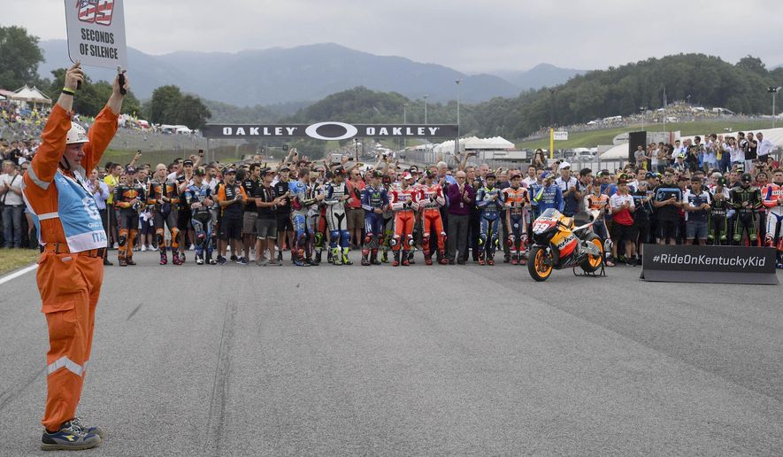 Riders observe 69 seconds of silence to pay their homage to Nicky Hayden, the American motorcycle rider who died after been hitting by a car while training on his bicycle in central Italy, prior to the start of the Moto3 Italian Grand Prix, at the Mugello circuit in Scarperia, Italy, Sunday, June 4, 2017. (Luca Zennaro/ANSA via AP)