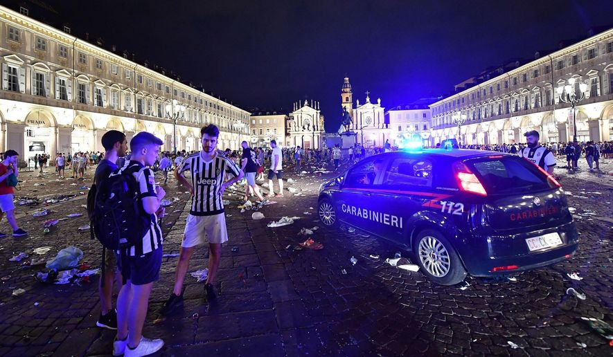 Juventus fans stand near a Carabinieri car, Italian paramilitary police, as they leave San Carlo's square at the end of the Champions League final soccer match between Juventus and Real Madrid, in Turin, Italy, Saturday, June 3, 2017.  Juventus fans watching the Champions League final rushed out of a Turin piazza in panic Saturday after witnesses reported hearing a loud sound. (Alessandro Di Marco/ANSA via AP)