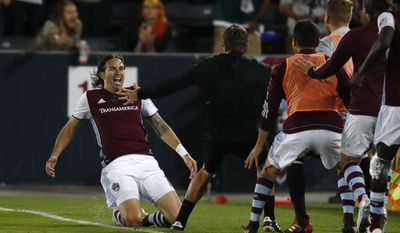 Colorado Rapids forward Alan Gordon, left, slides on the pitch as he celebrates after scoring the go-ahead goal against the Columbus Crew in the second half of an MLS soccer game Saturday, June 3, 2017, in Commerce City, Colo. (AP Photo/David Zalubowski)