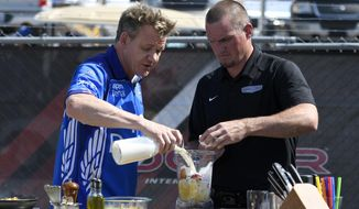 "British celebrity chef Gordon Ramsay, left, films a segment of his show ""The F word"" before the NASCAR Cup series auto race, Sunday, June 4, 2017, at Dover International Speedway in Dover, Del. At right is tire changer Eric Maycroft. (AP Photo/Nick Wass)"