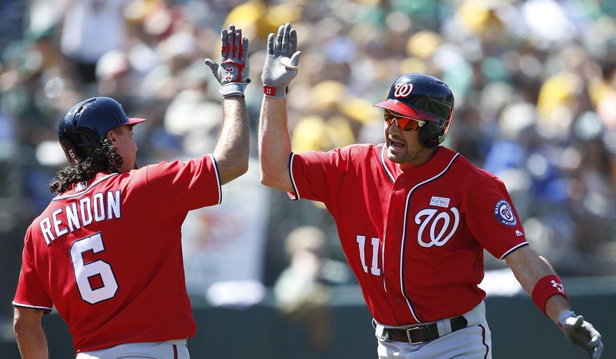 Washington Nationals' Ryan Zimmerman (11) celebrates with teammate Anthony Rendon (6) after hitting a three-run home run against the Oakland Athletics during the eighth inning of a baseball game on Sunday, June 4, 2017, in Oakland, Calif. (AP Photo/Tony Avelar)