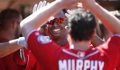 Washington Nationals' Michael Taylor, center, celebrates with teammate Daniel Murphy after hitting a solo home run against the Oakland Athletics during the ninth inning of a baseball game on Sunday, June 4, 2017, in Oakland, Calif. (AP Photo/Tony Avelar)