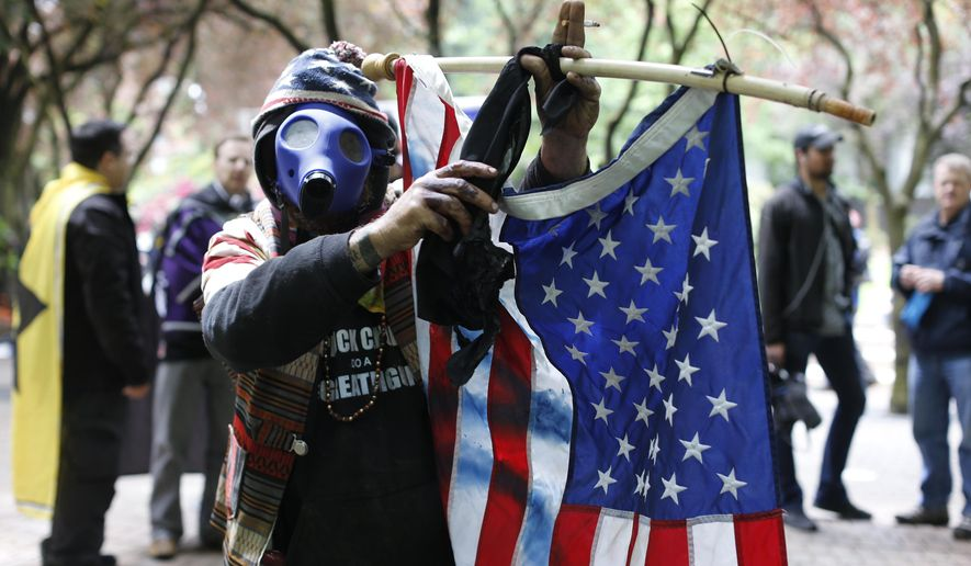 John Durano, who says he flew in from LA to participate and demonstrate his white pride, wears a gas mask and waves an American flag during a demonstration near City Hall and adjacent parks in  Portland, Sunday, June 4, 2017. Crowds have swelled to several thousand as demonstrators from varying groups have converged in downtown Portland.  (Beth Nakamura/The Oregonian via AP)