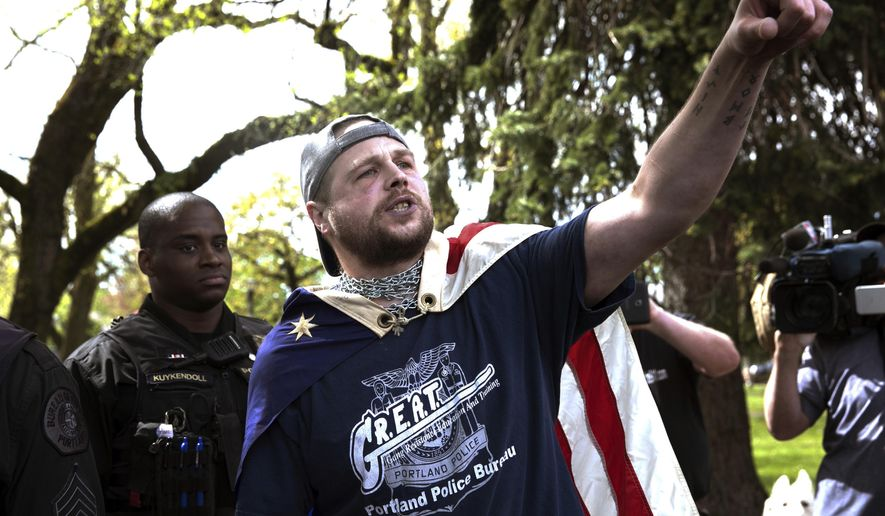 FILE - In this April 29, 2017, file photo provided by John Rudoff, Jeremy Joseph Christian, right, talks during a Patriot Prayer organized by a pro-Trump group in Portland, Ore. Christian, the man accused of stabbing two commuters to death who tried to stop him from hurling anti-Muslim insults at young women on a light-rail train came from a stable family and was a rambunctious teenager who spiraled out of control as he entered his teenage years, according to court records and acquaintances.(John Rudoff via AP, File)