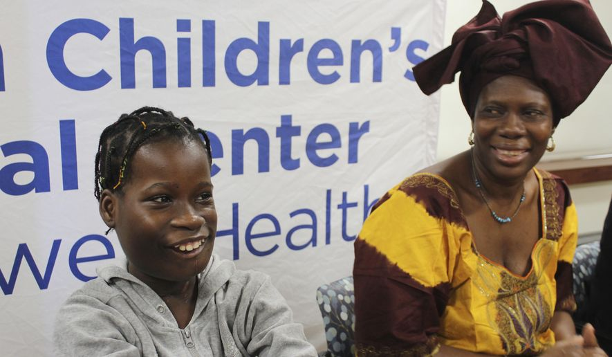 Janet Sylva, left, and her mother, Philomena, smile during a press conference at Cohen Children's Medical Center in New Hyde Park, N.Y., on Thursday, March 9, 2017. Surgeons removed a 6-pound tumor that had been growing in the 12-year-old girl's mouth during a procedure at the medical center in January. The girl and her mother, who are from the West African nation of Gambia, were brought to the United States for the free surgery by the charity The Global Medical Relief Fund. Surgeons said the tumor was one of the largest they had ever seen and had prevented the girl from eating and made breathing difficult. (AP Photo/Frank Eltman).