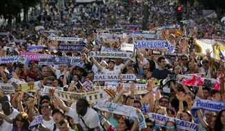 Fans celebrate in Cibeles square while waiting for Real Madrid players to arrive after they won the Champions League final, Madrid, Spain, Sunday June 4, 2017. Real Madrid became the first team in the Champions League era to win back-to-back titles with their 4-1 victory over Juventus in Cardiff Saturday. (AP Photo/Paul White)