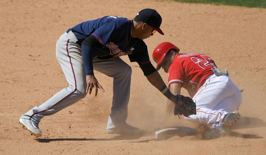 Los Angeles Angels' Ben Revere, right, is tagged out by Minnesota Twins shortstop Ehire Adrianza while trying to steal second during the ninth inning of a baseball game, Sunday, June 4, 2017, in Anaheim, Calif. Revere was initially called safe, but the call was overturned after review which ended the game. (AP Photo/Mark J. Terrill)