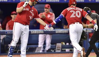 Toronto Blue Jays third baseman Josh Donaldson, right, is congratulated by teammate Kendrys Morales after hitting a solo home run against the New York Yankees during eighth inning American League baseball action in Toronto, Sunday, June 4, 2017. (Frank Gunn/The Canadian Press via AP)