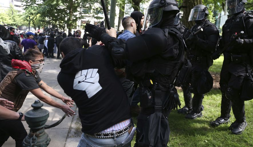 Police officers move to clear demonstrators from Chapman Square in downtown Portland, declaring it an unlawful assembly, near City Hall in downtown Portland, June. 4, 2017. (Dave Killen/The Oregonian via AP)