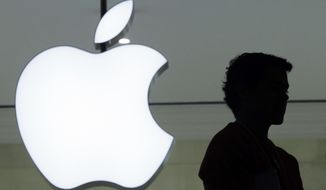 In this Wednesday, Dec. 7, 2011, file photo, a person stands near the Apple logo at the company's store in Grand Central Terminal, in New York. (AP Photo/Mark Lennihan, File)