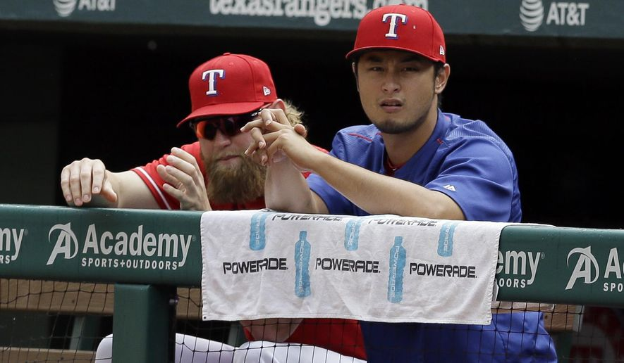 Texas Rangers starting pitcher Andrew Cashner and starting pitcher Yu Darvish, right, of Japan watch play against the Houston Astros in the fifth inning of a baseball game, Sunday, June 4, 2017, in Arlington, Texas. (AP Photo/Tony Gutierrez)