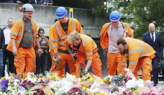 Construction workers leave flowers near the attack scene at London Bridge following Saturday's attack Monday June 5, 2017. (Isabel Infantes/PA via AP)