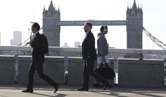 """Commuters cross London Bridge, which has reopened after Saturday evening's terror attack, in London Monday, June 5, 2017. London police have raided two addresses and detained """"a number"""" of people suspected of some connection to the Saturday night car attack and knife rampage on London Bridge. (Isabel Infantes/PA via AP)"""