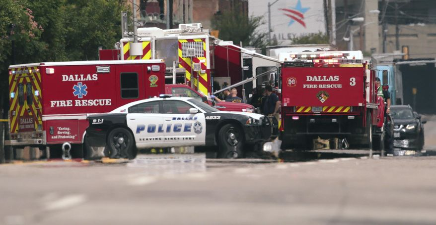 Emergency response crews gather on a closed street in front of the Dallas police headquarters in Dallas, Monday, June 5, 2017. A portion of the Dallas police headquarters has been evacuated and nearby streets closed after a suspicious package was found. (AP Photo/LM Otero)