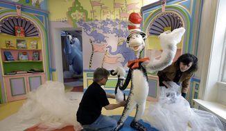 "In this May 4, 2017, photo John Simpson, left, project director of exhibitions for The Amazing World of Dr. Seuss Museum, and his wife Kay Simpson, right, president of Springfield Museums, unwrap a statue of the ""Cat in the Hat,"" at the museum, in Springfield, Mass. The museum devoted to Dr. Seuss, which opened on June 3 in his hometown, features interactive exhibits, a collection of personal belongings and explains how the childhood experiences of the man, whose real name is Theodor Geisel, shaped his work. (AP Photo/Steven Senne)"