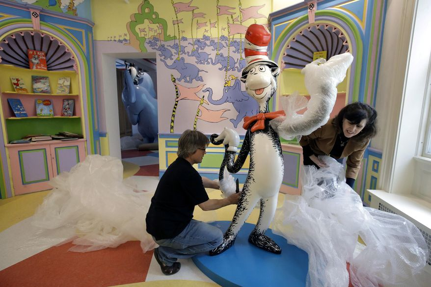 """In this May 4, 2017, photo John Simpson, left, project director of exhibitions for The Amazing World of Dr. Seuss Museum, and his wife Kay Simpson, right, president of Springfield Museums, unwrap a statue of the """"Cat in the Hat,"""" at the museum, in Springfield, Mass. The museum devoted to Dr. Seuss, which opened on June 3 in his hometown, features interactive exhibits, a collection of personal belongings and explains how the childhood experiences of the man, whose real name is Theodor Geisel, shaped his work. (AP Photo/Steven Senne)"""