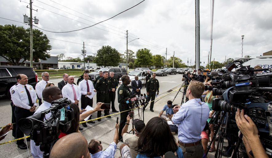 Orange County Sheriff Jerry Demings, center, addresses the media after a shooting at Fiamma, a business in Orlando on Monday, June 5, 2017. Authorities said there were multiple fatalities in an industrial area near Orlando, Fla. (Aileen Perilla/Orlando Sentinel via AP)