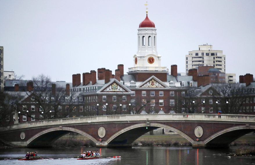 Rowers paddle along the Charles River past the Harvard College campus in Cambridge, Mass. (AP Photo/Charles Krupa, File)