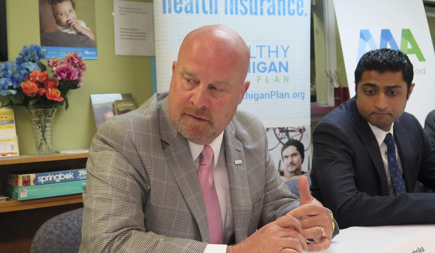 Michigan budget director Al Pscholka defends the state's Medicaid expansion program, Monday, June 5, 2017, during a briefing with reporters at the Care Free Medical and Dental Clinic in Lansing, Mich. At right is the clinic's CEO and medical director, Dr. Farhan Bhatti. Medicaid would undergo significant changes if a U.S. House-passed bill is enacted. (AP Photo/David Eggert)