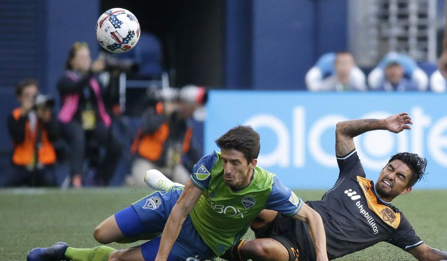 Seattle Sounders midfielder Alvaro Fernandez, left, and Houston Dynamo defender A. J. DeLaGarza go down as they battle for the ball in the first half of an MLS soccer match, Sunday, June 4, 2017, in Seattle. (AP Photo/Ted S. Warren)