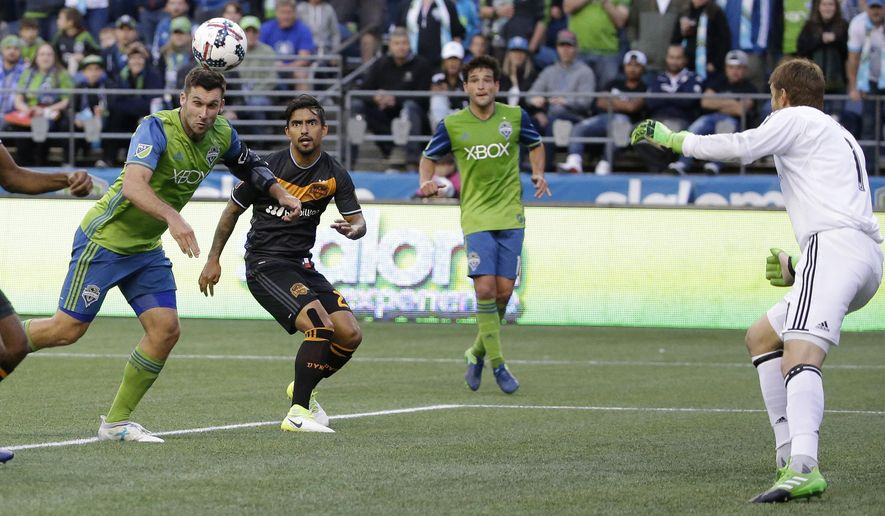 Seattle Sounders forward Will Bruin, left, heads the ball for a goal against Houston Dynamo goalkeeper Tyler Deric, right, in the second half of an MLS soccer match, Sunday, June 4, 2017, in Seattle. The Sounders won 1-0. (AP Photo/Ted S. Warren)