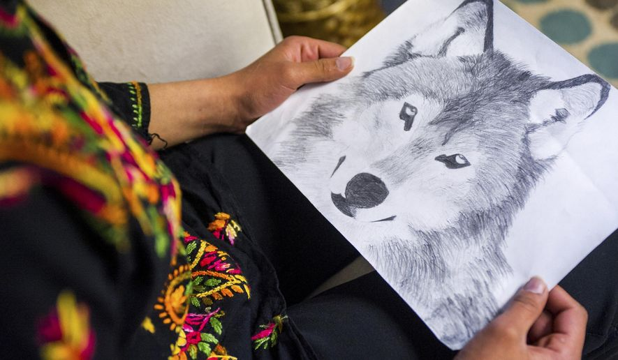 In a May 25, 2017 photo, a Lincoln North Star student from Afghanistan holds a drawing she made at her therapist's office. Lincoln Public Schools has a new program to help refugee students deal with the trauma that made them flee their home countries. (Amber Baesler/The Journal-Star via AP)