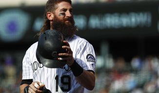 FILE - In this Tuesday, May 30, 2017, file photo, Colorado Rockies leadoff hitter Charlie Blackmon shakes out his helmet while waiting in the on-deck circle to face the Seattle Mariners in the first inning of an interleague baseball game in Denver. In spite of his idiosyncrasies, Blackmon has developed into one of the top leadoff hitters in the game. (AP Photo/David Zalubowski, File)