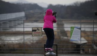 FILE - In this Feb. 14, 2016 file photo, a girl uses binoculars to watch the North side at the Imjingak Pavilion near the border village of Panmunjom, which has separated the two Koreas since the Korean War, in Paju, South Korea. A South Korean civic group said Monday, June 5, 2017, that North Korea has rejected its offer to provide anti-malaria supplies to protest Seoul's support of fresh U.N. sanctions on the country. (AP Photo/Lee Jin-man. File)