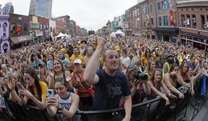 Fans watch a pre-game concert as they wait to watch Game 4 of the NHL hockey Stanley Cup Finals between the Nashville Predators and the Pittsburgh Penguins on Broadway Street in Nashville, Tenn., Monday, June 5, 2017. (AP Photo/Mark Humphrey)