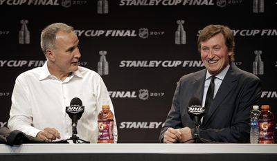 Hockey great Wayne Gretzky, right, answers a question as former teammate Paul Coffey, left, watches during a news conference before Game 4 of the NHL hockey Stanley Cup Finals between the Nashville Predators and the Pittsburgh Penguins Monday, June 5, 2017, in Nashville, Tenn. (AP Photo/Chuck Burton)