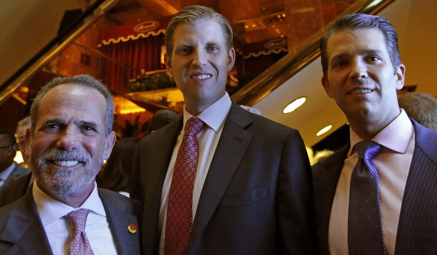 Eric Danziger, CEO of Trump Hotels, left, joins Eric Trump, center, and Donald Trump Jr., both of whom are executive Vice Presidents of The Trump Organization, as the trio poses for a photograph during an event for Scion Hotels, Monday, June 5, 2017, in New York. (AP Photo/Kathy Willens)