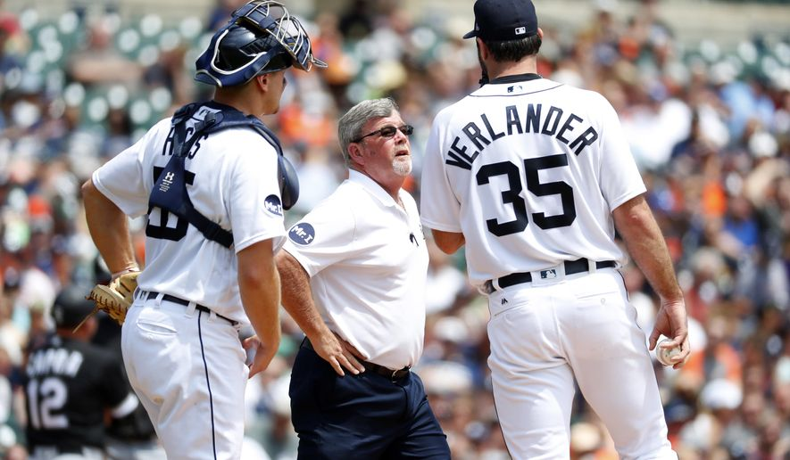 Detroit Tigers trainer Kevin Rand checks on pitcher Justin Verlander (35) as catcher John Hicks (55) looks on in the second inning of a baseball game in Detroit, Sunday, June 4, 2017. (AP Photo/Paul Sancya)