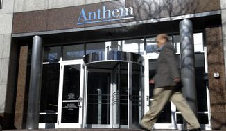 In this Thursday, Feb. 5, 2015, file photo, a man walks past health insurer Anthem's corporate headquarters in Indianapolis. (AP Photo/Michael Conroy, File)