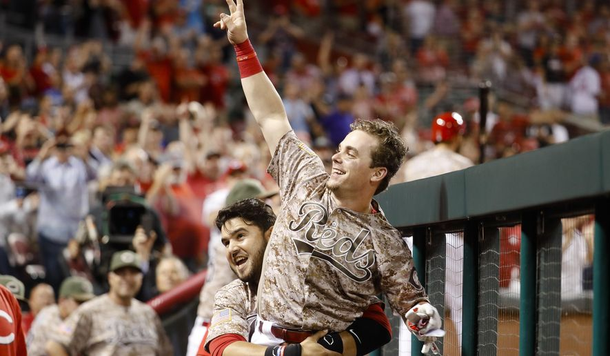 Cincinnati Reds' Scooter Gennett, center, is lifted up by Eugenio Suarez as he celebrates in the dugout during the eighth inning of a baseball game against the St. Louis Cardinals, Tuesday, June 6, 2017, in Cincinnati. The Reds won 13-1. (AP Photo/John Minchillo)
