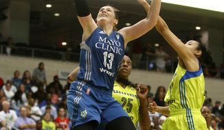 FILE - In this May 20, 2017, file photo, Minnesota Lynx guard Lindsay Whalen (13) lays up a shot against Dallas Wings forward Glory Johnson (25) and guard Saniya Chong (12) in the fourth quarter of a WNBA basketball game in Arlington, Texas. Minnesota is running through the league again and holds the top spot in The Associated Press WNBA power poll. (Rose Baca/The Dallas Morning News via AP, File)