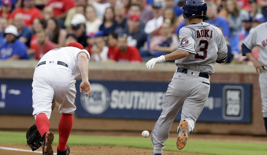 Texas Rangers first baseman Mike Napoli is unable to field the throw to the bag as Houston Astros' Norichika Aoki (3) reaches on a single to second during the fourth inning of baseball game, Saturday, June 3, 2017, in Arlington, Texas. Aoki advanced to second on the throwing error by second baseman Rougned Odor. (AP Photo/Tony Gutierrez)