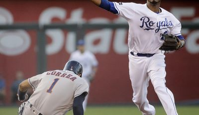 Kansas City Royals shortstop Alcides Escobar throws to first too late for the double play after forcing Houston Astros' Carlos Correa (1) out at second on a force out hit into by Carlos Beltran during the third inning of a baseball game Tuesday, June 6, 2017, in Kansas City, Mo. (AP Photo/Charlie Riedel)
