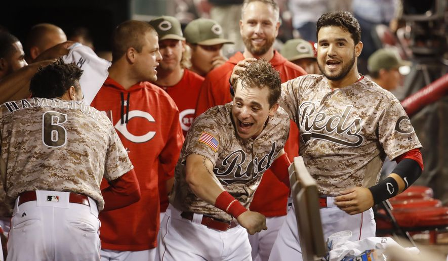 Cincinnati Reds' Scooter Gennett, center, celebrates in the dugout after hitting a two-run home run and his fourth overall in the eighth inning of a baseball game against the St. Louis Cardinals, Tuesday, June 6, 2017, in Cincinnati. The Reds won 13-1. (AP Photo/John Minchillo)