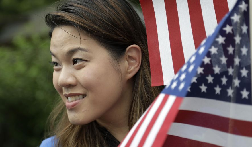 "In this May 29, 2017, photo, Christine Lui Chen,, who is running for state senate during the November elections, participates in the Bridgewater Memorial Day Parade in Bridgewater, N.J. Chen, a 36-year-old health care executive in New Jersey and mother of two small children, had never considered entering politics, focusing instead on her family, her career and her community. That all changed in January, when she attended the Women's March on Washington. Thirteen hours later, she emailed Democratic officials: ""Here's my resume. I want to get involved."" (AP Photo/Julio Cortez)"