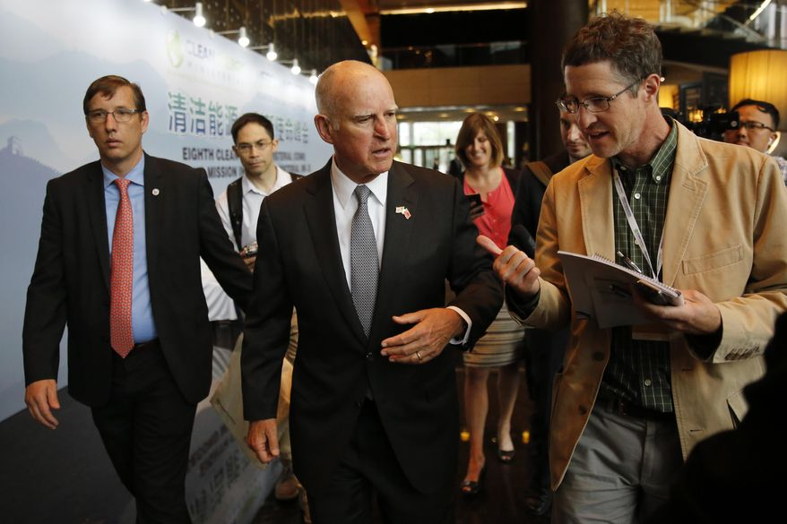 California Gov. Jerry Brown, center, talks with reporters after delivering a speech during the Clean Energy Ministerial International Forum on Electric Vehicle Pilot Cities and Industrial Development, at a hotel in Beijing, Tuesday, June 6, 2017. Brown predicts that President Donald Trump's decision to pull the U.S. out of the Paris climate accord will prove temporary because of the urgency of the issue. He told The Associated Press on the sidelines of a clean energy conference in Beijing on Tuesday that China, Europe and U.S. state governors will for now fill the gap left by the federal government's move to abdicate leadership on the issue. (AP Photo/Andy Wong)