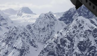 FILE - This April 24, 2016, file photo taken above the Kahiltna Glacier near Denali, shows peaks in the Alaska Range, as seen through the open cargo bay doors of a Chinook helicopter. Rangers rescued two climbers in unrelated incidents from Kahiltna Glacier in Denali National Park on Monday, June 5, 2017. (AP Photo/Mark Thiessen, File)