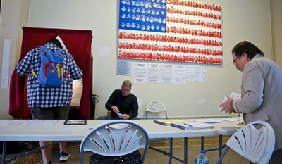 Poll station administrators Michael Barron, center, and Ira Landgarten, right, work as a voter enters the booth at City Hall, during primary voting for New Jersey gubernatorial candidates, Tuesday June 6, 2017, in Hoboken, N.J. (AP Photo/Bebeto Matthews)