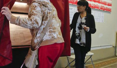 Poll station administrator Leticia Velez, right, watches as a voter enters the booth at City Hall, during primary voting for New Jersey gubernatorial candidates, Tuesday June 6, 2017, in Hoboken, N.J. (AP Photo/Bebeto Matthews)