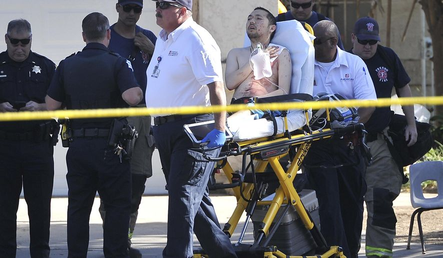 A shooting victim is taken away from a house, Tuesday, June 6, 2017, in Fresno, Calif. Fresno police reported that four people were shot in an east-central neighborhood Tuesday morning. (John Walker/The Fresno Bee via AP)