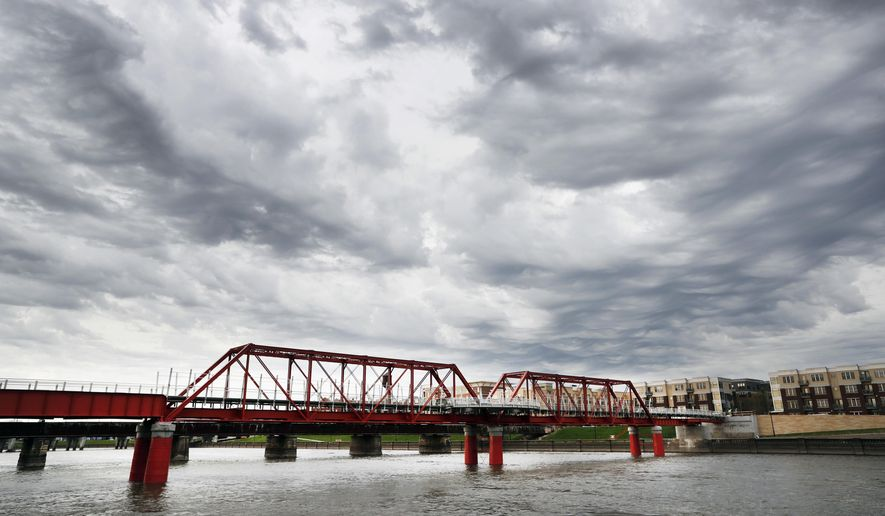 In this April 18, 2017, photo, the Red Bridge pedestrian bridge is seen over the Des Moines River in Des Moines, Iowa. A little more than a decade after it was restored, crews went back to the site with a crane to hoist the span more than 4 feet higher, at a cost of $3 million, after experts concluded that the river's flooding risk was double the previous estimates. (AP Photo/Charlie Neibergall)